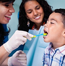 Dentist and mother helping a child brush his teeth