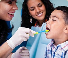 Dentist brushing a child's teeth