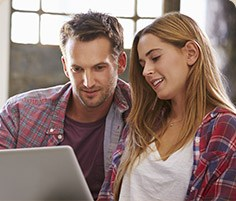 Couple wearing flannel shirts looking at a computer
