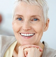 Short haired woman in her 60's wearing dentures