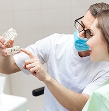 Dentist and patient looking at model implant bridge