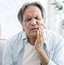 older man with jaw pain from bruxism