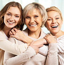 Woman from three generations holding each other smiling